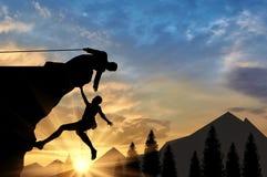 Bergsteiger hilft dem Freund, der Handreichung im Gebirgssonnenuntergang gibt lizenzfreie abbildung