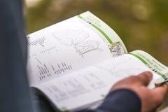 Bergsteiger holdin ein topo-Buch in seinen Händen Lizenzfreies Stockfoto