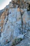Bergsteiger klettern oben die steile Klippe Stockfoto
