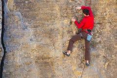 Bergsteiger klettert den Felsen Stockfotografie