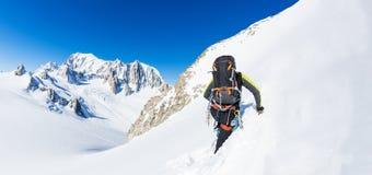 Bergsteiger klettert eine schneebedeckte Spitze Im Hintergrund die Gletscher und Stockbilder