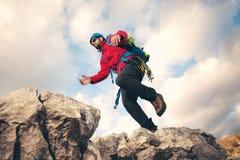 Bergsteiger springt über Felsen im mountin Lizenzfreie Stockfotografie