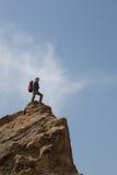 Bergsteiger steht oben Stockbild