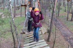 Bergsteigeranfang des kleinen Mädchens der Durchgang ropes Kurs Stockfotos