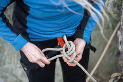 Bergsteigerfrau, bei der Sicherheitsgurtbindung fangen Palstekknoten ein lizenzfreie stockfotos