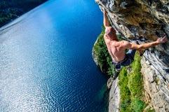 Bergsteigermann über dem See Stockfotografie