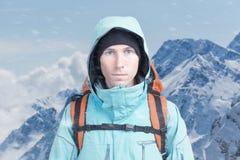 Bergsteigermann steht im Schneesturm, Berglandschaft im Hintergrund Stockfotografie