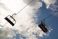 Bergstolskidlift på blå himmel med vita moln Fotografering för Bildbyråer