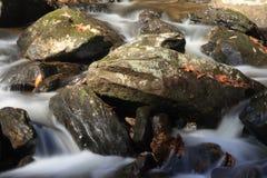 Bergstroom die over rotsachtige grond stromen die cascades maken stock foto's