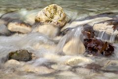 Bergstroom die tussen de stenen stromen die en met bruine de herfstbladeren begroet royalty-vrije stock afbeelding