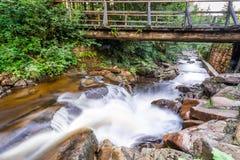 Bergstroom en een oude houten brug Stock Afbeelding