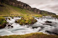 bergstroom in het midden van een weide in IJsland stock afbeelding