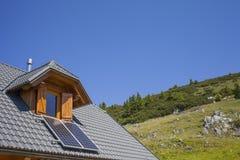 Bergstuga med solpaneler Arkivbild