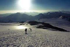 Bergturister stiger ned från Mount Elbrus till passerandet Soyuzmultfilm Arkivbilder