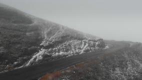 Bergväg i Georgia som går till passerandet i dåligt väder i dimma och snö arkivfilmer