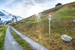 Bergväg i schweiziska fjällängar Arkivfoto
