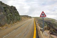 Bergväg, krökning för dubblett för trafikvarningstecken Royaltyfri Foto