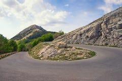 Bergväg med 180 grad vänd Montenegro sikt av den Lovcen nationalparken Arkivfoton