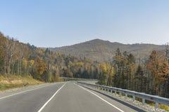 Bergväg på långt - den östliga taigaen Royaltyfri Bild