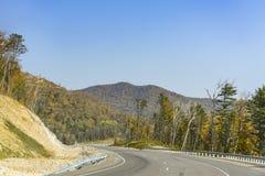 Bergväg på långt - den östliga taigaen Arkivfoto