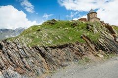 Bergväg som leder till den georgiska kristna kyrkan Arkivbild