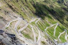 Bergväg som omges av gröna kullar royaltyfri foto