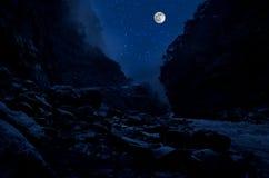 Bergväg till och med skogen på en fullmånenatt Sceniskt nattlandskap av mörker - blå himmel med månen _ arkivbilder