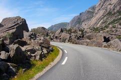 Bergvägen between vaggar och enorma stenblock norway Arkivbilder