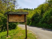 Bergvägmärke som göras ut ur trä bredvid vägen arkivfoton
