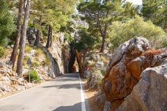 Bergvägväg som går in i en stentunnel nära by Sa Calobra Ö Majorca, Spanien Arkivfoton