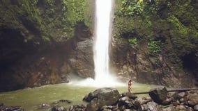Bergvattenfallet för den flyg- sikten i djungelskog och resande flickaanseende på vaggar Turist- flicka i bikini på tropiskt lager videofilmer