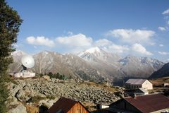 Bergwaarnemingscentrum met zonne radiotelescoop tegen de achtergrond van sneeuwbergen stock foto