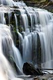 Bergwaterval het dalen over vlotte mosrotsen royalty-vrije stock afbeeldingen