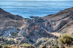 Bergweg die afgelopen ruwe rotsachtige klippen winden stock afbeelding