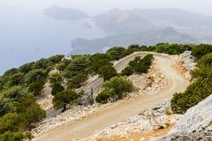 Bergweg onder bomen en stenen Op de horizon - eilanden i royalty-vrije stock afbeelding
