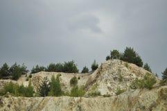 Bergwerk mit Bäumen und einem Sturmhimmel Stockfotografie