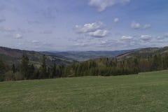Bergwiese und bewölkter Himmel Lizenzfreies Stockbild
