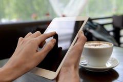 Berühren Sie eine Tablette im café mit einem Tasse Kaffee Stockfoto