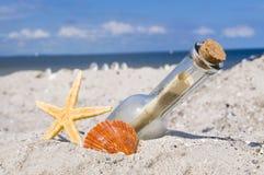 Bericht in een fles met hout, bord en maritieme decoratie stock foto's