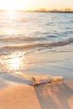 Bericht in een fles op strand met zonsondergang en onduidelijk beeld de industrie backg Stock Foto's