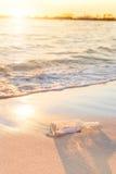 Bericht in een fles op strand met zonsondergang en onduidelijk beeld de industrie backg Royalty-vrije Stock Foto's