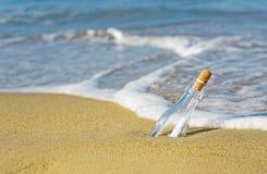 Bericht in een Fles op strandoverzees Royalty-vrije Stock Afbeelding