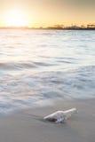 Bericht in fles op strand met zonsondergang en onduidelijk beeld de industriebackgro Royalty-vrije Stock Afbeeldingen