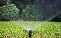 Berieseln Sie die Bewässerung des Rasens in einem Park, bokeh Hintergrund Lizenzfreie Stockfotos