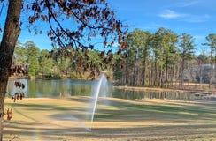 Berieselungsanlage auf dem Golfplatz mit Regenbogen stockbild