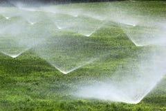 Berieselungsanlagen auf einem grünen Rasen lizenzfreie stockfotografie