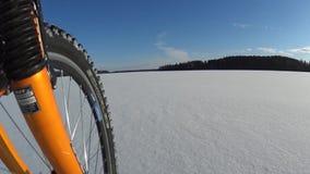 Berijdende fiets op bevroren meer stock videobeelden