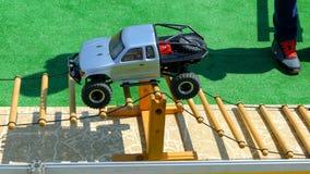Berijdt de stuk speelgoed radio-Gecontroleerde jeep een hindernis op het spoor stock footage