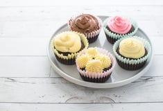 Berijpt cupcakes op witte plaat op houten lijst stock foto's