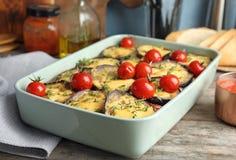 Beringela cozida com tomates e queijo no dishware foto de stock